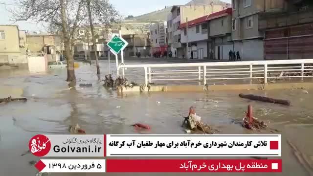 تلاش کارمندان شهرداری خرم آباد برای مهار طغیان رودخانه کرگانه